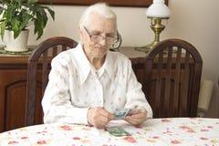 计数金钱的老妇人,当坐在桌上时 库存照片
