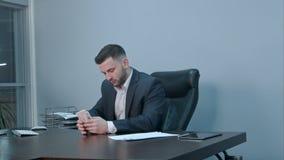 计数他的金钱的成功的商人坐在办公室 免版税库存照片