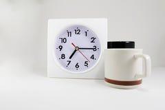 计时与在白色backgound的两个咖啡杯 库存照片