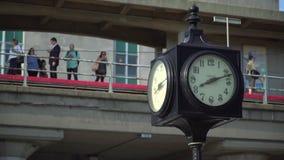 计时在与等待在火车站的通勤者的前景