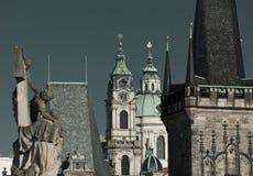 计时在查尔斯桥梁塔围拢的圣尼古拉斯教会钟楼  免版税库存照片