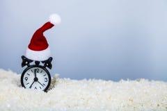 计时在雪的一个圣诞老人帽子 免版税库存照片
