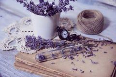 计时测量的时钟旧书和淡紫色花 库存图片
