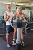 计时他的锻炼脚踏车的教练员客户在健身房 免版税库存图片