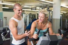 计时他的锻炼脚踏车的教练员客户在健身房 库存图片