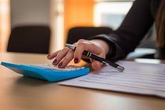 计算一张发货票的女商人在她的办公室 免版税库存照片