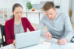 计算他们的费用和收入的年轻夫妇 图库摄影