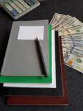 计算器、书和100美金 库存照片