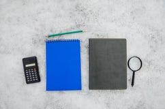 计算器、放大器、铅笔和笔记本在白色背景 免版税库存照片