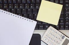 计算器、智能手机和片剂在膝上型计算机键盘,特写镜头 图库摄影