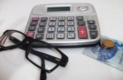 计算器、玻璃和金钱从白色背景 图库摄影
