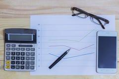 计算器、电话、笔和玻璃在财政图表,事务c 免版税库存照片