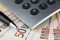 计算器、笔和欧元特写镜头在桌上 免版税库存图片