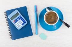 计算器、笔记薄、笔、橡皮擦、咖啡在蓝色杯子和匙子 库存照片