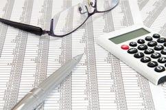 计算器和圆珠笔和玻璃和会计凭证 免版税库存照片