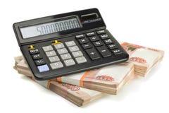 计算器和堆金钱 库存照片