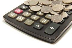 计算器和硬币在白色背景 库存图片