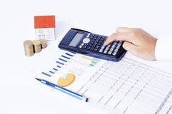 计算器和笔在企业图与硬币堆和房子纸 库存图片