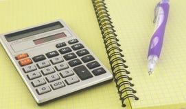 计算器和笔在文字书 免版税库存图片