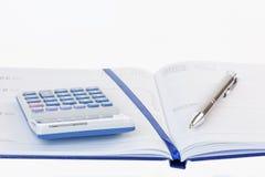 计算器和笔在日志 免版税图库摄影