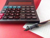 计算器和笔在纸笔记薄 图库摄影