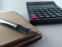 计算器和笔在纸笔记薄 免版税库存图片