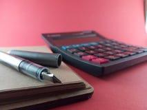 计算器和笔在纸笔记薄 免版税图库摄影