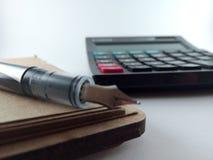 计算器和笔在纸笔记薄 免版税库存照片
