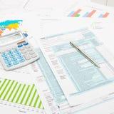 计算器和笔在美国1040报税表和一些财政图-接近的演播室射击 库存图片