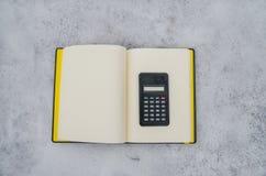 计算器和笔记本在雪 免版税库存照片