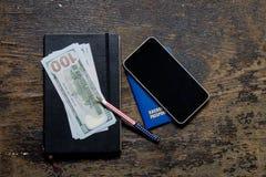 计算器和笔记薄护照笔美元电话 免版税库存照片
