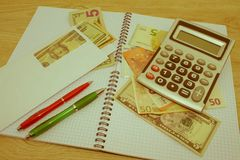 计算器和金钱在木桌上 财政规划,储款的概念 免版税库存图片