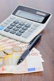 计算器和金钱在桌上 免版税库存图片