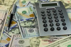 计算器和金钱在美元背景说谎  事务的想法和概念 免版税库存照片
