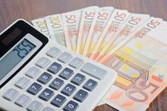 计算器和钞票在桌上 免版税库存照片