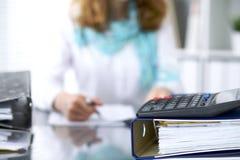 计算器和黏合剂与纸等待由女实业家或秘书后面处理在迷离 内部 免版税库存图片