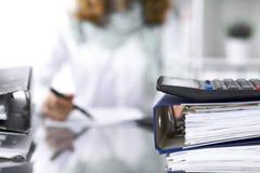 计算器和黏合剂与纸等待由女实业家或秘书后面处理在迷离 内部 免版税库存照片