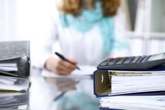 计算器和黏合剂与纸等待由女实业家或秘书后面处理在迷离 内部 图库摄影