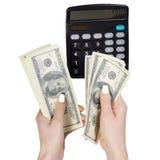 计算器在手中金钱美元 库存照片