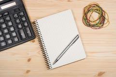 计算器笔记本和笔在木办公桌上 免版税库存图片