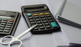 计算器,剪刀,在桌上的笔记本 库存照片