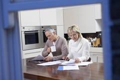 计算国内汇票的夫妇在厨房用桌上 库存图片