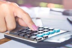 计算她的月度费用的女商人手在税期间晒干 免版税库存图片
