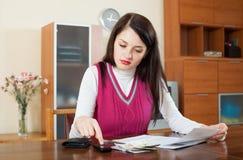 计算家庭预算的严肃的妇女 免版税库存照片