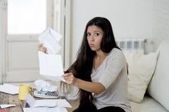 计算月度费用的年轻有吸引力的拉丁妇女客厅长沙发在重音在家担心 库存图片