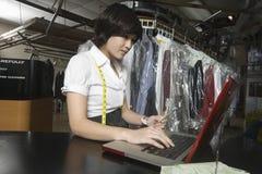 计算有膝上型计算机的妇女比尔在洗衣店 免版税库存图片