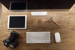 计算机、剪刀和照相机的图片在运转的书桌上 库存图片