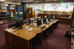 计算机书桌在图书馆里 免版税库存照片