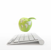 计算机和与世界地图的一个苹果 库存图片