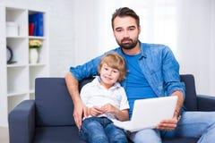 计算机和互联网概念-年轻父亲和小的儿子usin 免版税图库摄影